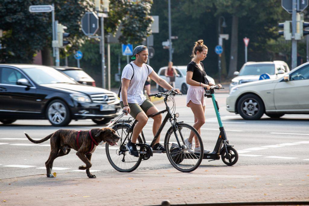 Pärchen unterwegs auf einem Fahrrad und Elektroroller