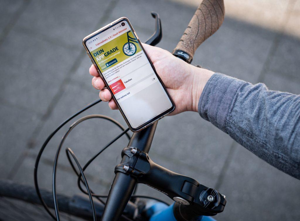Ein Fahrradfahrer schaut auf sein Handy.