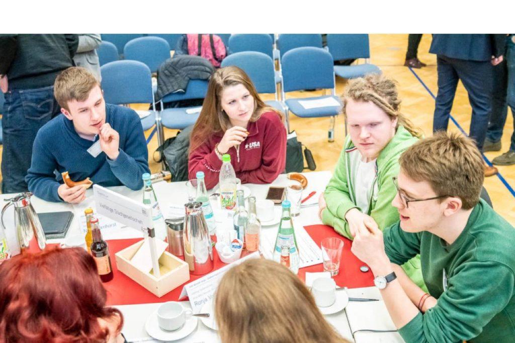 Gruppe junger Menschen sitzen an einem Tisch und diskutieren offensichtlich über ihre Interessen.