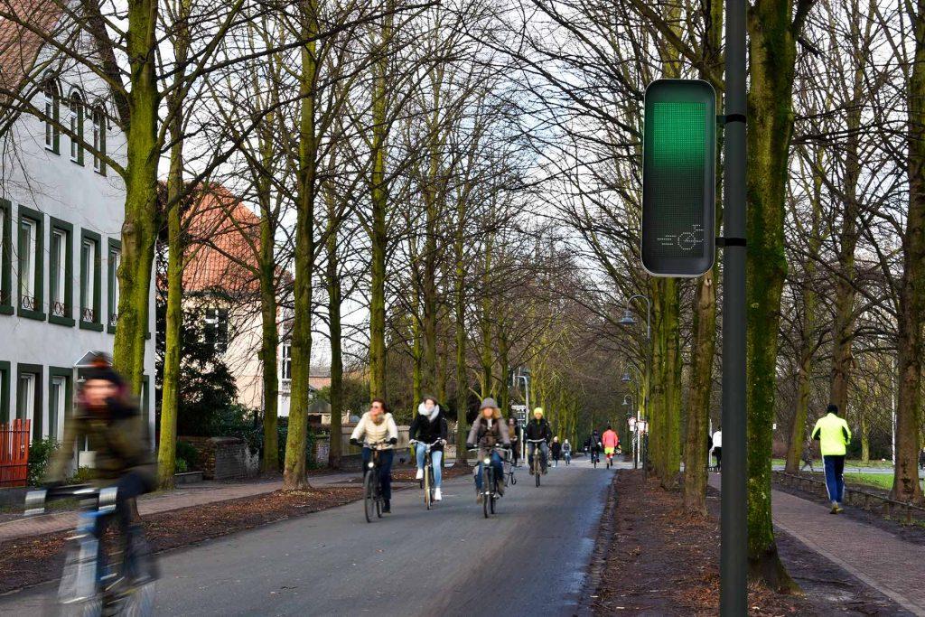 """LED-Display vor der Ampel signalisiert, wie schnell Radfahrende in die Pedale treten müssen, um möglichst entspannt auf der """"Grünen Welle"""" zu reiten."""