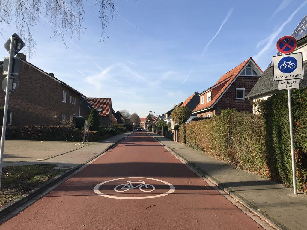 Ein in rot geteerter Fahrradweg durch eine Wohnsiedlung.